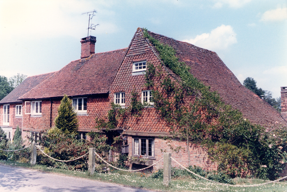 17th-century cottage with catslide roof on the right; repeated extensions to the left in the 18th century (Felbridge).
